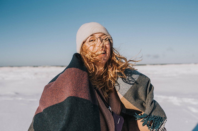 zimowa sesja na plaży dziewczyna czapka uśmiech